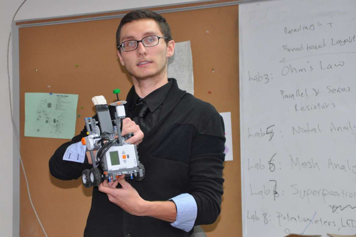 William Richards, Shepherd Robotics Club president, holds a Lego firefighter robot built from a Mindstorms NXT kit.