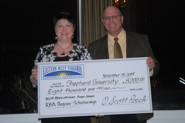 Beth Thomas, R.B.A. and continuing education program coordinator at Shepherd's Martinsburg Center, receives a check from Scott Roach, Eastern Panhandle Community Foundation board president, that will provide scholarships for R.B.A. students enrolled in the program in the spring of 2015.