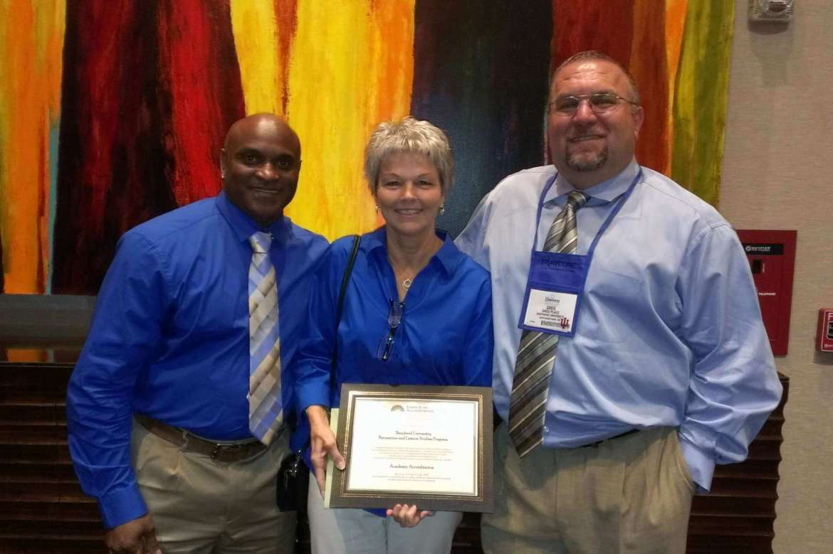 Professors from the Department of Health, Physical Education, Recreation and Sport display the accreditation certificate the department recently received. (left to right) D.r Andro Barnett, associate professor, Dr. Stacey Kendig, department chair, and Dr. Greg Place, assistant professor.