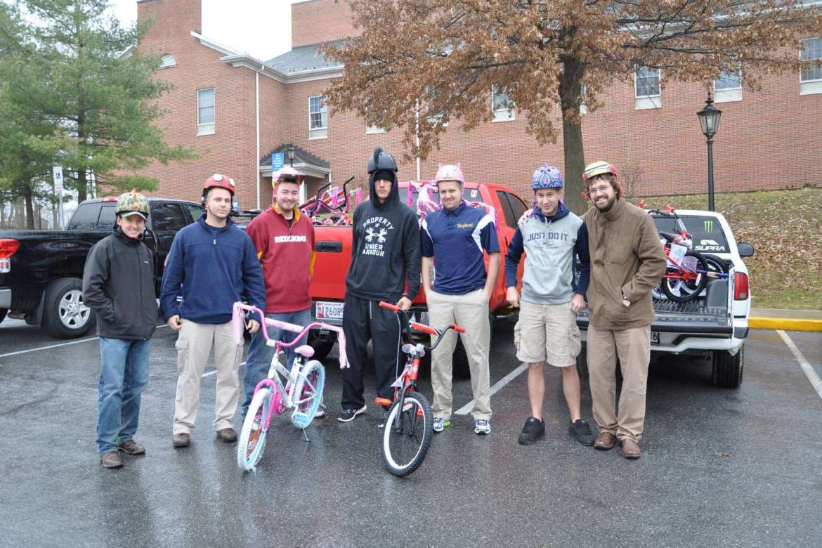 """Students from Shepherd University's health and physcial education program who organized """"Peddling for Success"""" pose with bikes and helmets that they donated to deserving children in Jefferson County. They are (left to right) Corey Mongam, Hagerstown, Maryland; Aaron Staats, Winchester, Virginia; Bobby Lanham, Charles Town; Nate Socke, Middletown, Maryland; Will Jenkins, Inwood; Daniel Powell, Hagerstown, Maryland; and  and Dr. Jared Androzzi, assistant professor of physical education."""