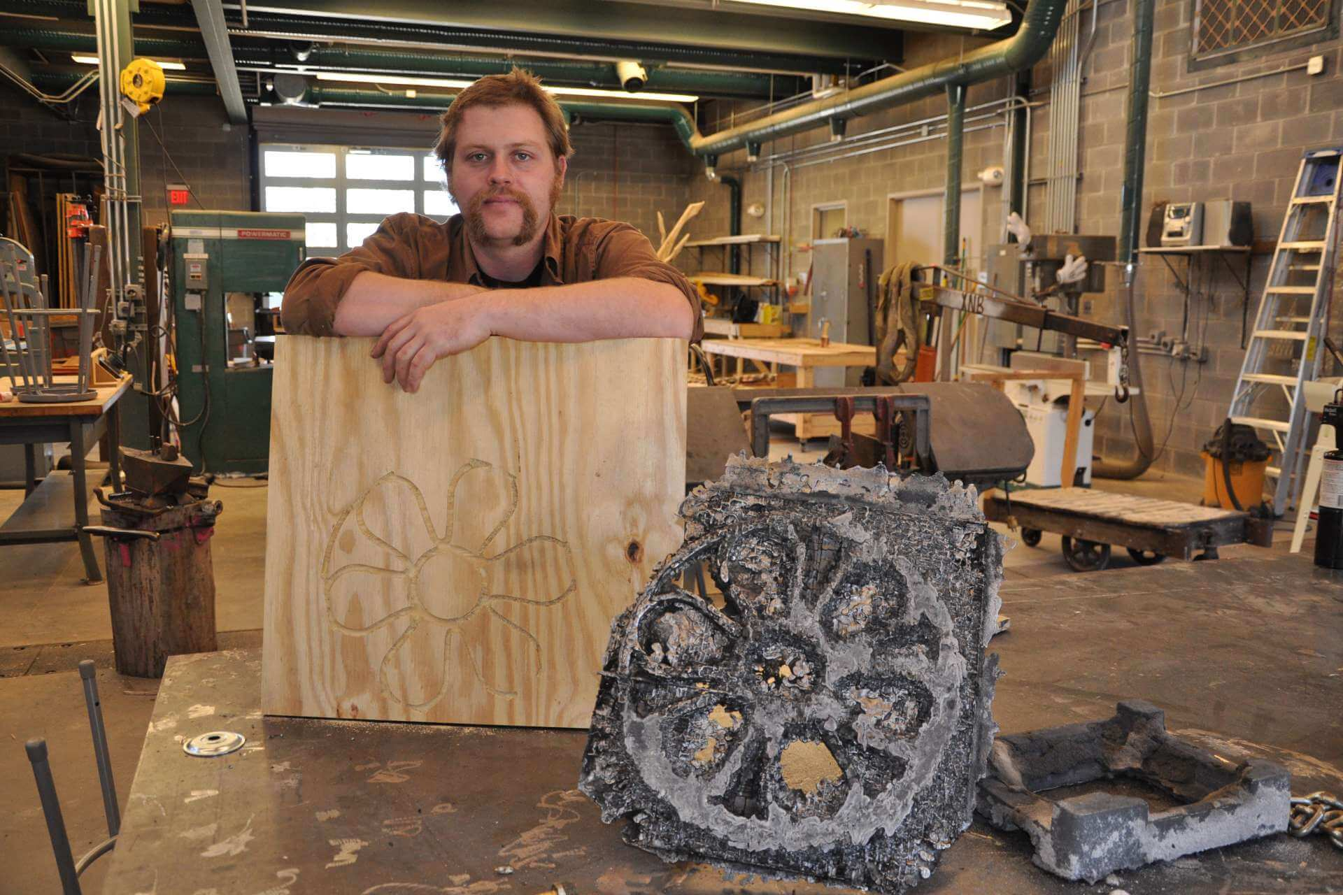 Christian Benefiel, assistant professor of art, makes scuptures from a variety of materials. During the most recent metal pour event he created molds from wood.
