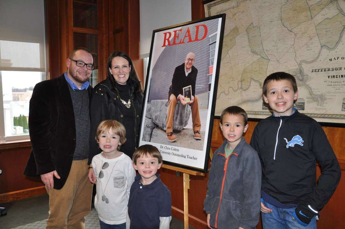 """Dr. Chris Coltrin, assistant professor of art history, poses with his wife Liz and four sons, Eli, McKay, Isaac and Will, in front of the Shepherd University Scarborough Society READ poster featuring him and his favorite book,  """"Les Misérables,"""" by Victor Hugo."""