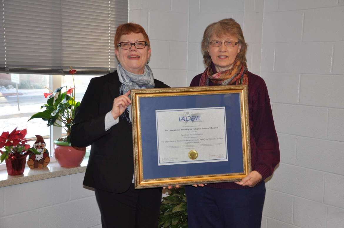 Dr. Kathleen Corpus, chair of the business administration and family and consumer sciences department, and Dr. Ann Marie Legreid, dean of Shepherd's School of Business and Social Sciences, display the certificate of accreditation from the International Assemby for Collegiate Business Education for Shepherd's bachelor of science in business administration and master's of business administration.