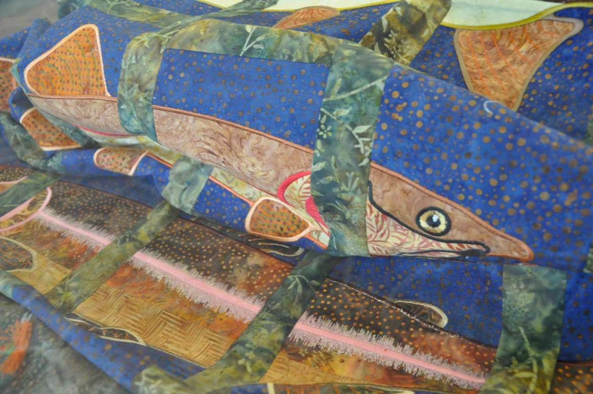 The trout quilt was made by Dennis Minnick using a computer program called machine applique, where the machine outlines a shape, the quilter inserts the fabric, and the machine sews the quilt together.