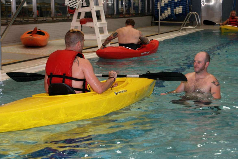 Christopher Price, student and Team River Runner volunteer, stands in the water in Shepherd's pool as he helps a member learn kayaking skills.