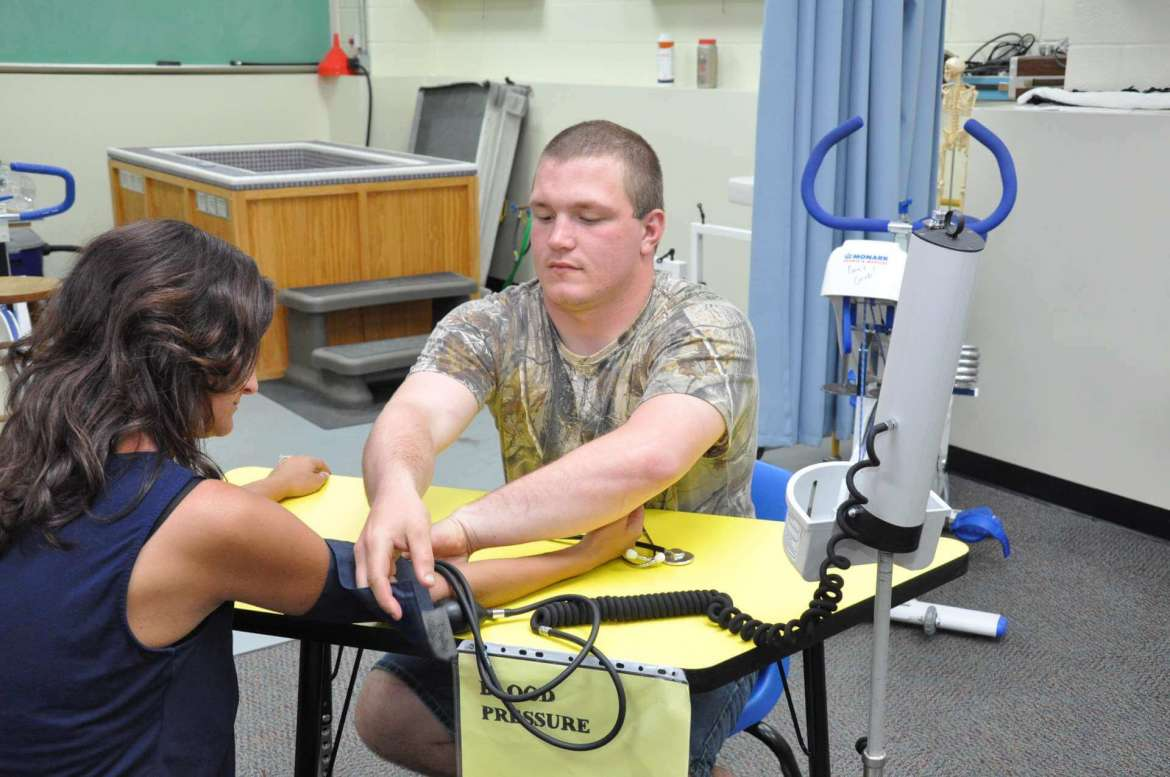 Junior Mark Bean of Clear Brook, Virginia, a recreation and sports studies major, practices taking blood pressure in the human performace lab on Jessica Graham, clinical faculty and director of the lab.