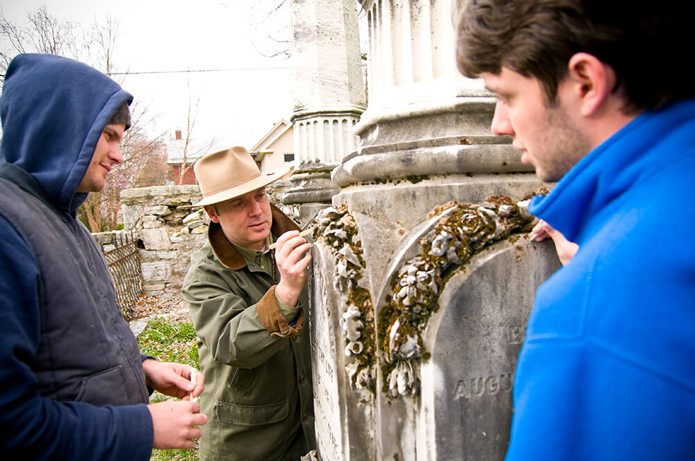 Dr. Keith Alexander, assistant professor of history, shows students how to clean the stones without causing damage.