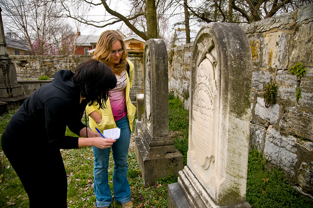 Students transcribe the information on the stones.