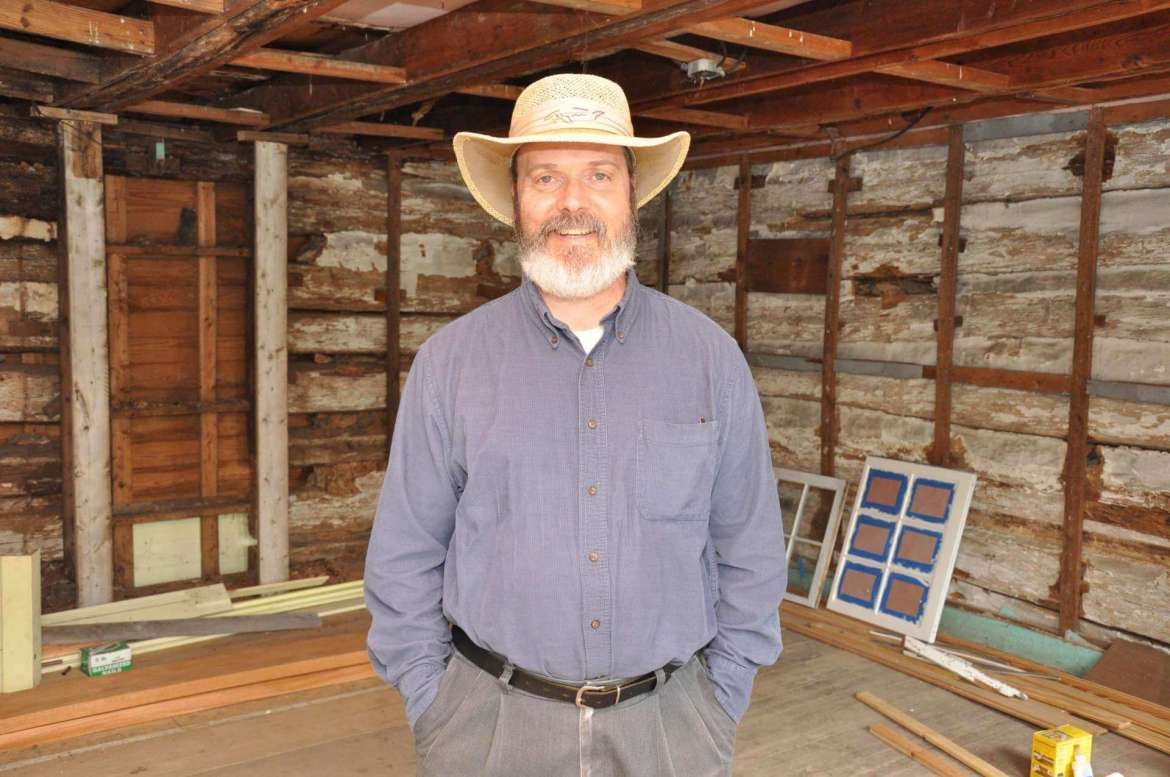 Dr. Keith Alexander, assistant professor of history, stands in the Yellow House, also known as the Entler-Weltzheimer House.