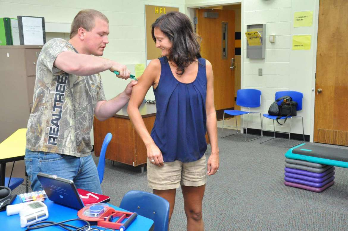 Junior Mark Bean of Clear Brook, Virginia, a recreation and sports studies major, practices doing a pinch test in the human performace lab on Jessica Graham, clinical faculty and director of the lab.