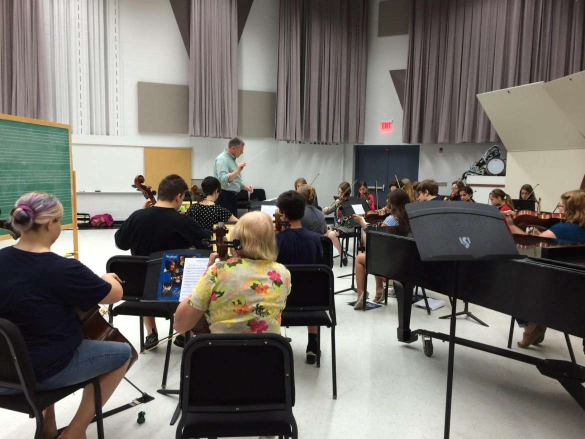 Dr. Scott Hippensteel, assistant professor of music and director of bands, works with students attending the 2014 String Orchestra Camp.