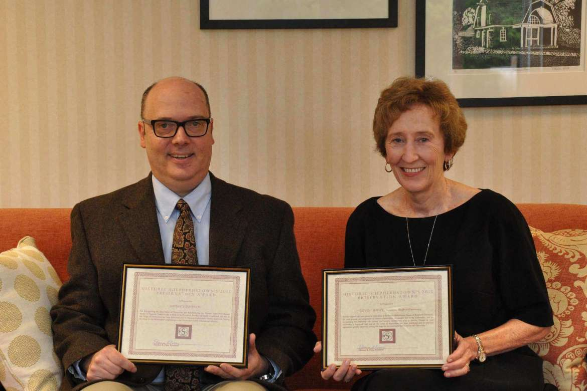 Dr. Keith Alexander (left), assistant professor of history, and Dr. Suzanne Shipley, university president, display the certificates naming Shipley and Shepherd University the 2015 Preservation Awards presented by the Historic Shepherdstown Commission. The awards recognize Shepherd's efforts to restore the Yellow House, also known as the Entler-Weltzheimer House.