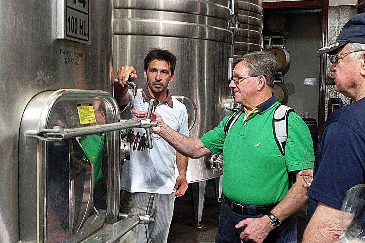 John Sheely, of Martinsburg, who went to Mendoza, Argentina, on the lifelong learning trip this past February, samples wine-in-progress from a tank at Bodega Gimenez Riili Winery located in the Uco Valley region.