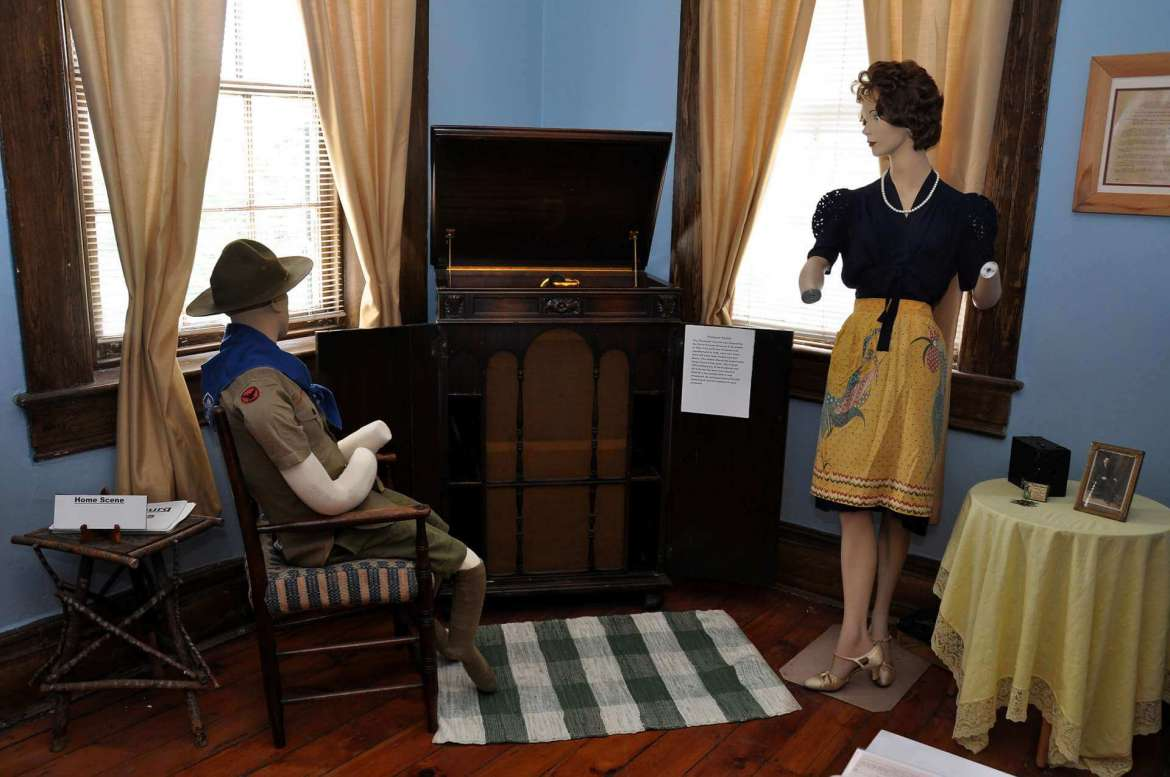 Shanholtzer's favorite part of the exhibit is the home scene. It includes a Victrola Credenza that plays old 78-speed records. A mannequin dressed as a Boy Scout sits in a chair in front of the Victrola and a mannequin standing nearby is dressed as a mom. The scene represents what a home might have been like when dad was off fighting the war.