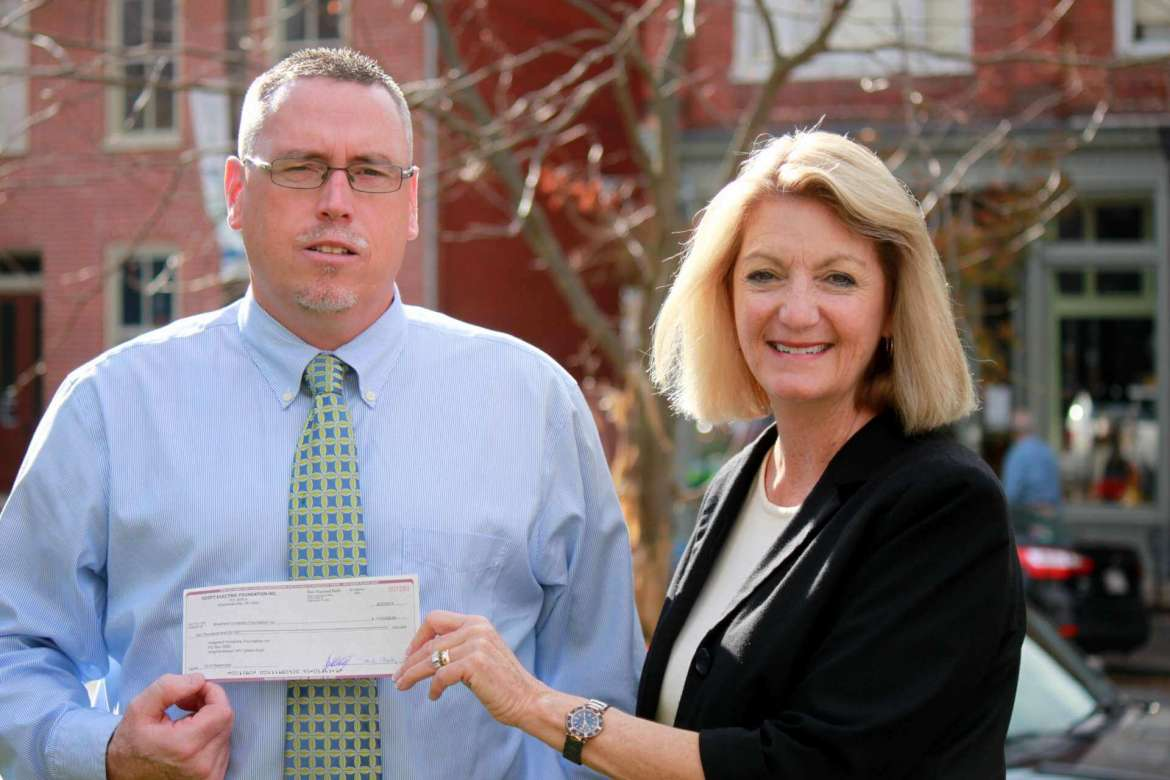 Monica Lingenfelter, executive vice president of the Shepherd University Foundation, accepts a $20,000 gift from Rusty Potts, a commercial outside sales representative for Scott Electric.