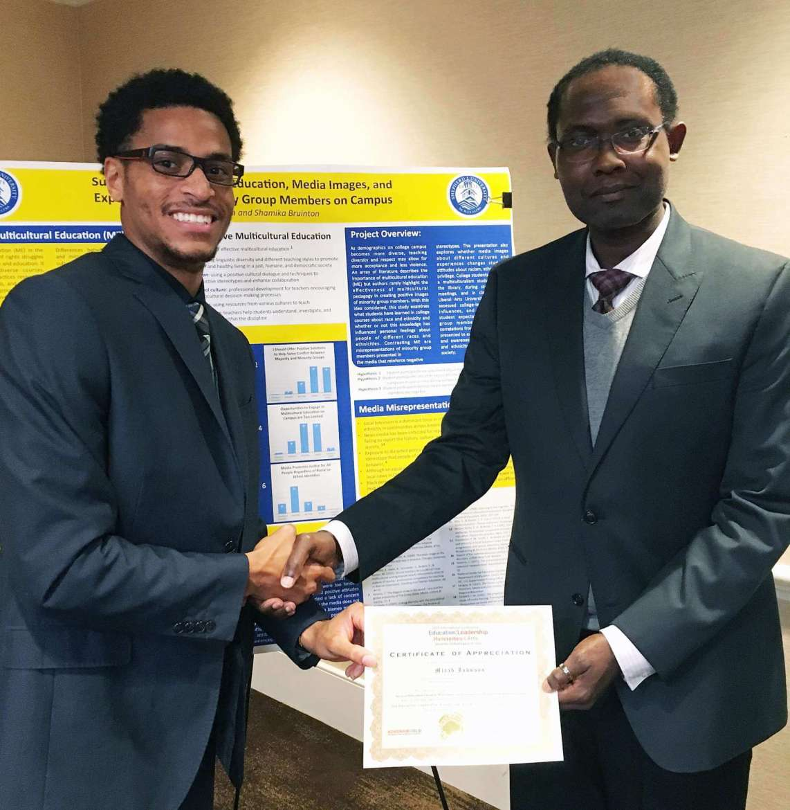 a development and administration master's major from Austin, Texas, (left) receives a certificate of appreciation from Eric Schwartz, executive director of Advena World LLC, for research he presented at the Advena World International Conference December 9 in Washington, D.C.
