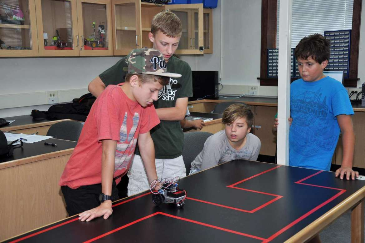 Students in the robotics camp test whether a robot has been programmed well enough to stay within the lines.