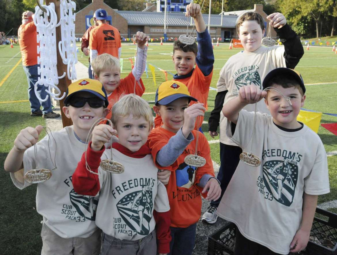 Cub Scouts from Pack 33 hold up mdeals they will present ot runners at the finish line Sat. morning in Shepherdstown. See more photos on CU.journal-news.net. (Journal Photo by Ron Agnir)