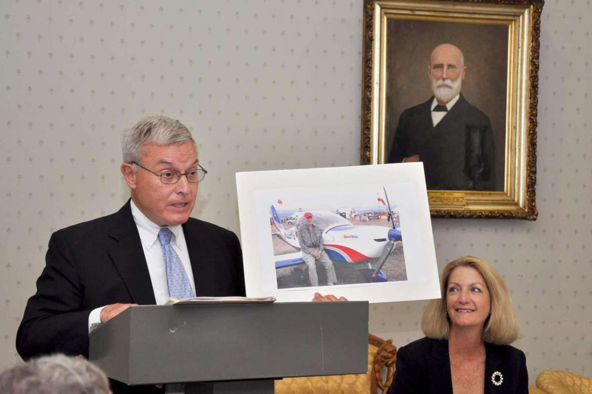 Richard McCune, Martinsburg attorney, holds a photo of T. Guy Reynolds and his airplane just before presenting a $222,000 gift to the Shepherd University Foundation.