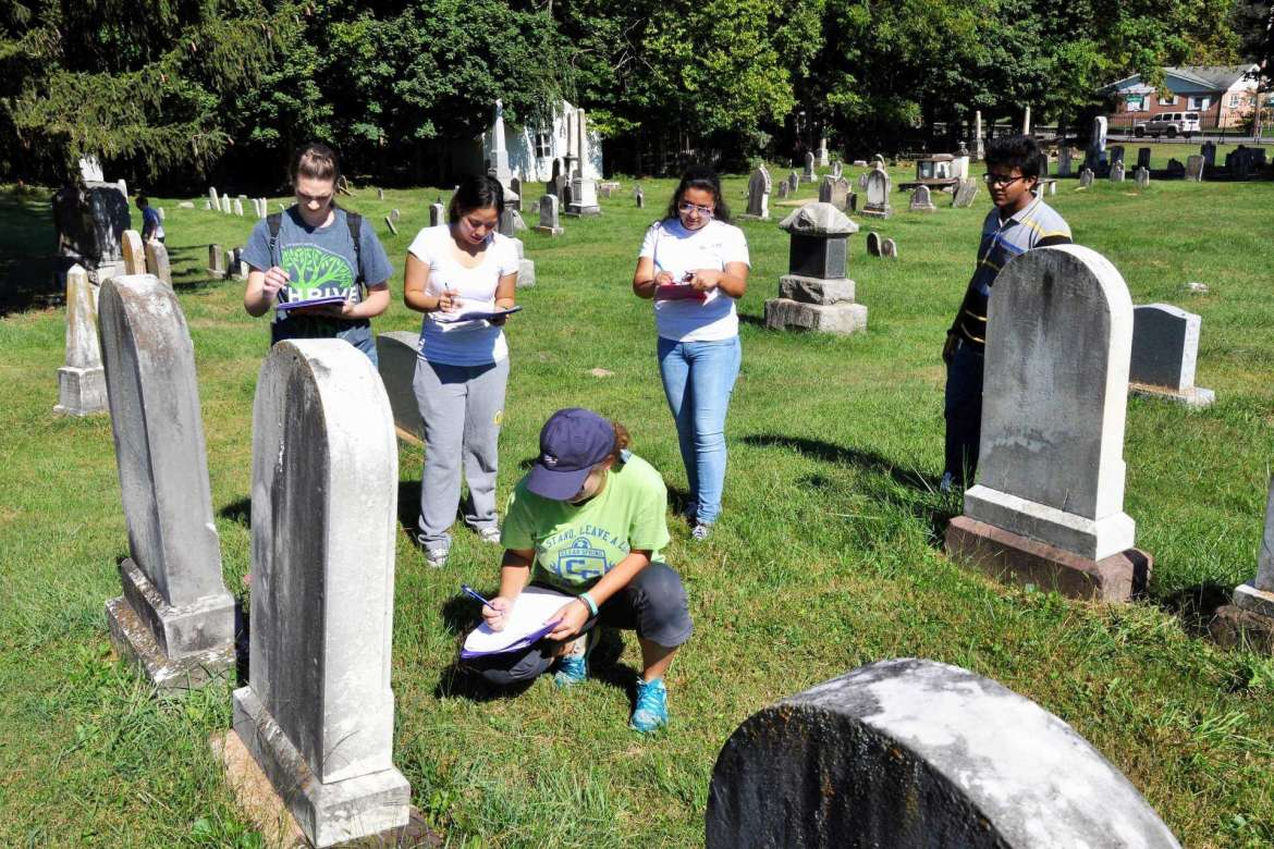 Elizabeth Boyer (kneeling) works with classmates (standing, l-r) Kayla Eury , Audrey Delos Santos, Joshua Franklin, and Bridget Colina to gather the birth and death dates of people buried in Elmwood Cemetery for a project in their general ecology class.