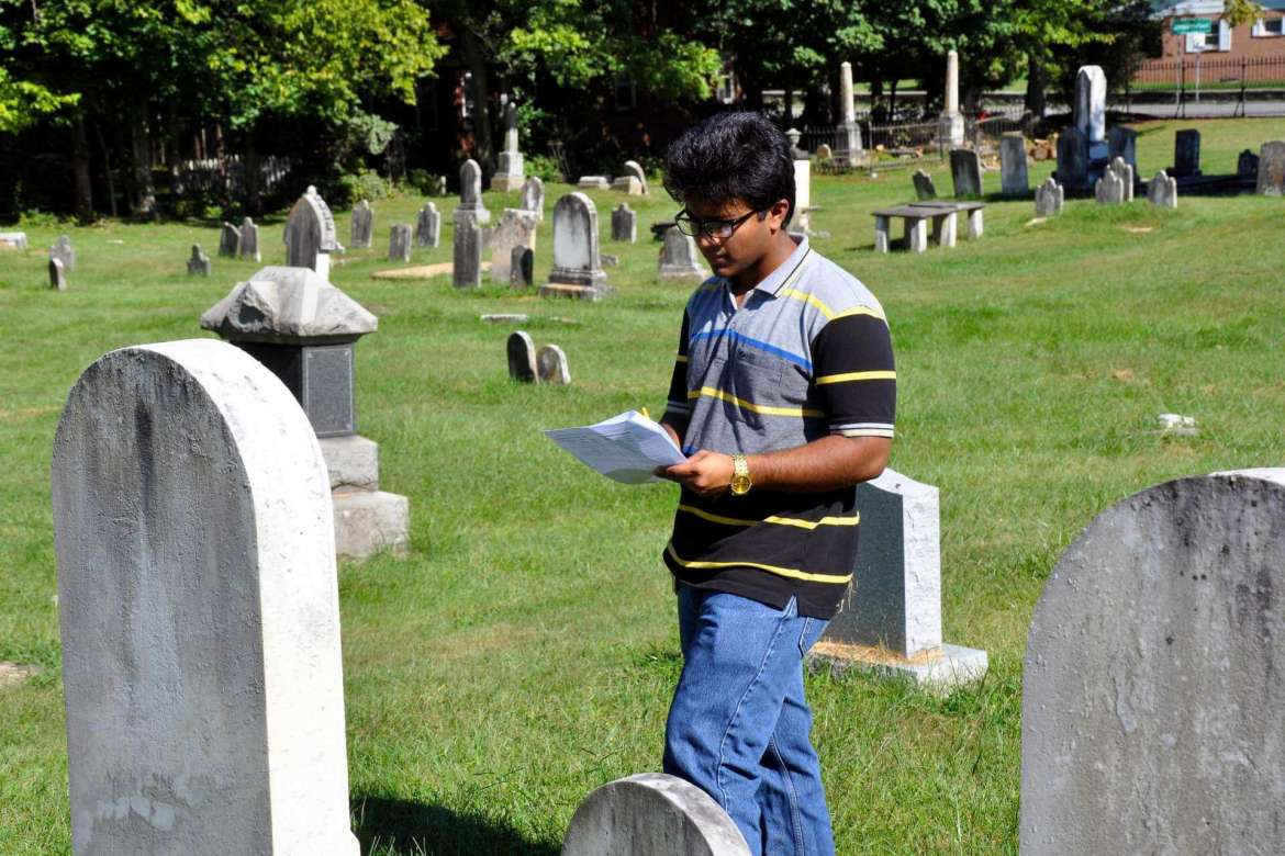 Joshua Franklin writes information down that is on one of the grave stones in Elmwood Cemetery.
