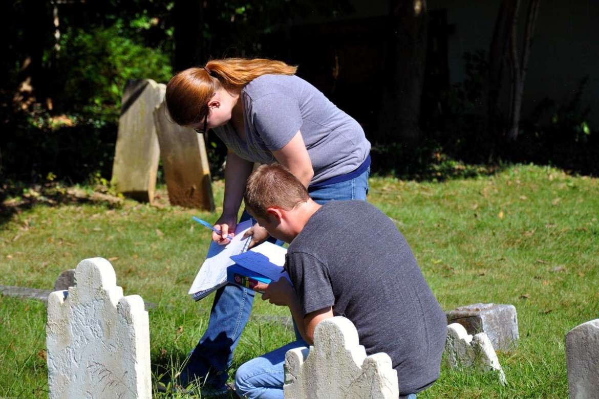 Marshall Hoffmaster and Jennifer Korcsmaros gather information from grave stones in Elmwood Cemetery for their general ecology class.