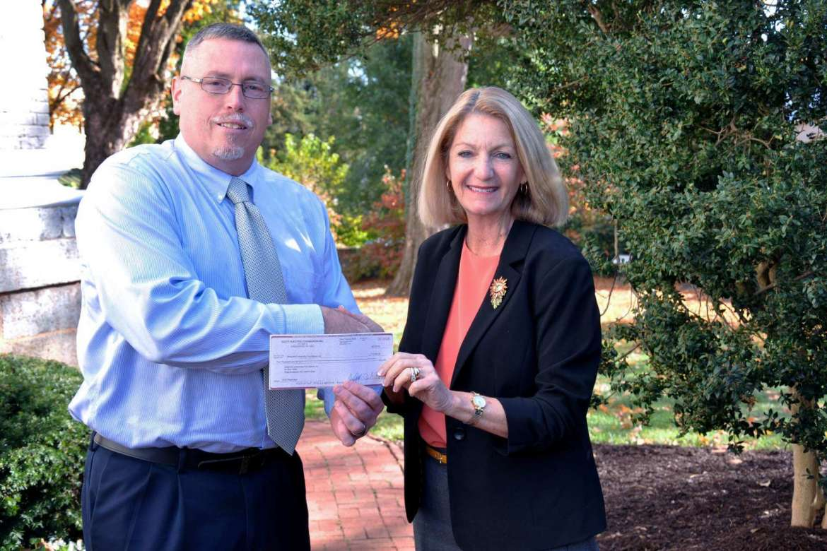 Monica Lingenfelter, executive vice president of the Shepherd University Foundation, accepts a $10,000 gift from Rusty Potts, a commercial outside sales representative for Scott Electric, a regional wholesale electrical wholesale distributor based out of Greensburg, Pennsylvania.