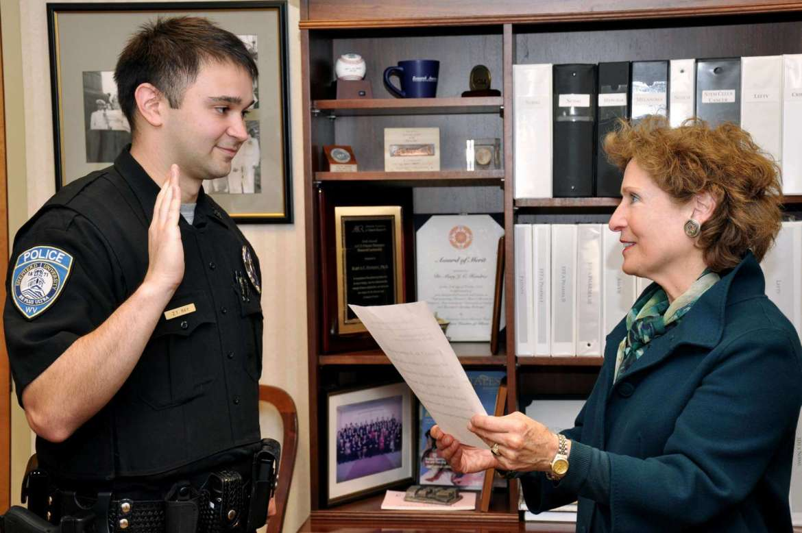 Shepherd University President Dr. Mary J.C. Hendrix (right) gives the oath of office to Shepherd's newest police officer, Zachary Ray.