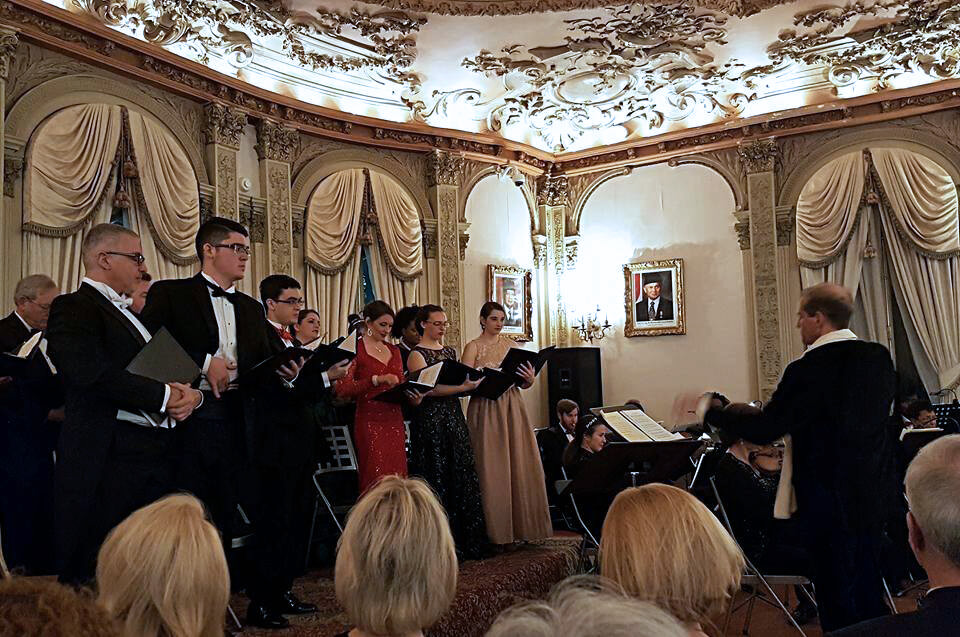 """Dr. Scott Beard (right), Shepherd University's associate provost, conducts the chorus during the """"Holiday Gala of Grand Opera"""" at the Embassy of the Republic of Indonesia in Washington, D.C., on December 9. Beard, who is artistic director for the Washington Opera Society Orchestra, produced the show, which also featured Shepherd adjunct faculty member Natalie Conte, soprano."""