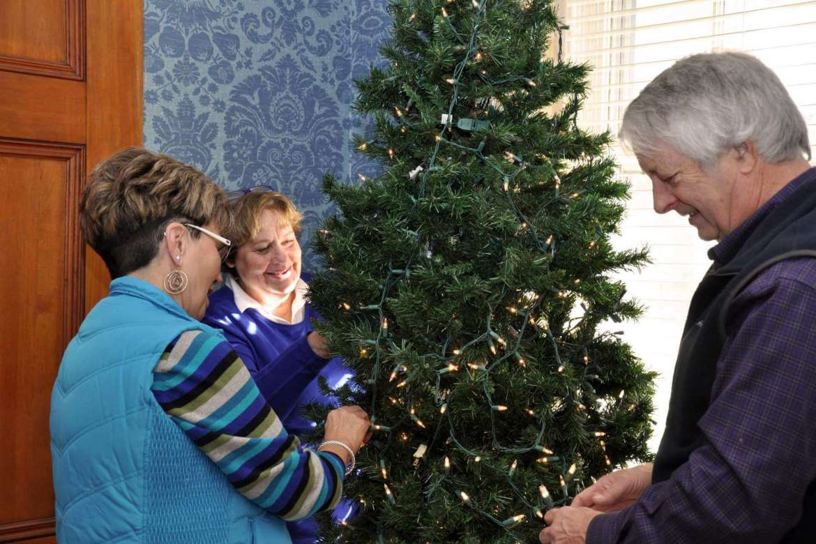 Peachy Staley (left), works with Barb and Jim Gibson to put lights on one of the two trees used to decorate Popodicon for the holidays.