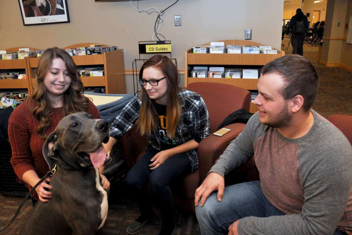 PurposeFULL Paws great dane puppy Nako visits with (l-r) Michaela Sencindiver, a history major from Inwood; Michalla Benton, a communications major from Dawsonville, Georgia; and Austin McClain, a physical therapy major from Huntington.