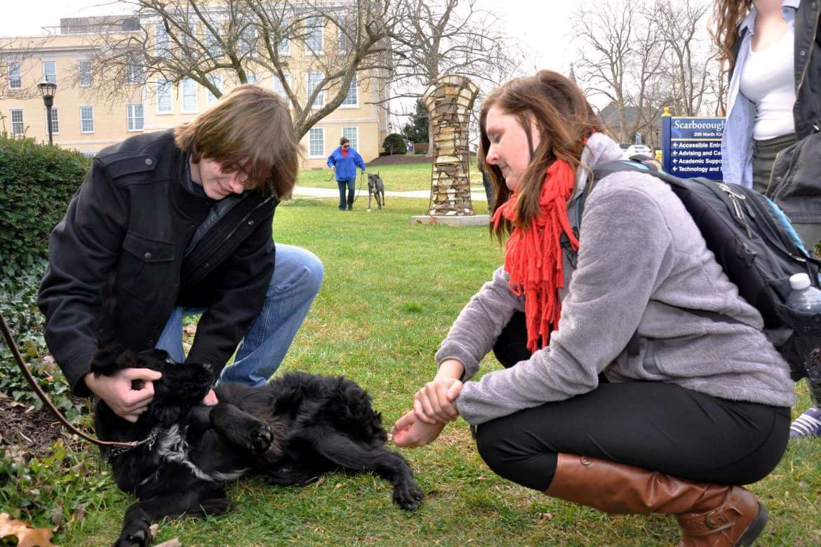 Ben Slappey, (left) a computer information sciences major from Fairfax, Virginia, and Andrea Cooper, a graphic design major from Bridgeport, pet one of the puppies from PurposeFULL Paws that visited campus Friday.