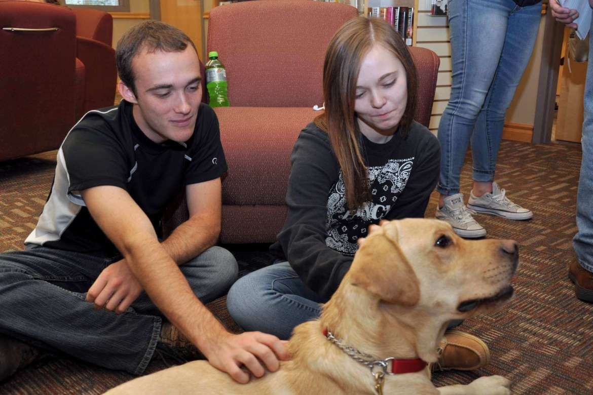 Oden, a yellow lab puppy from PurposeFULL Paws enjoys some attention from (l-r) Jonathan Wenner, a psychology major from Harpers Ferry, and Raechel MeGargee, a biology major from Berkeley Springs.
