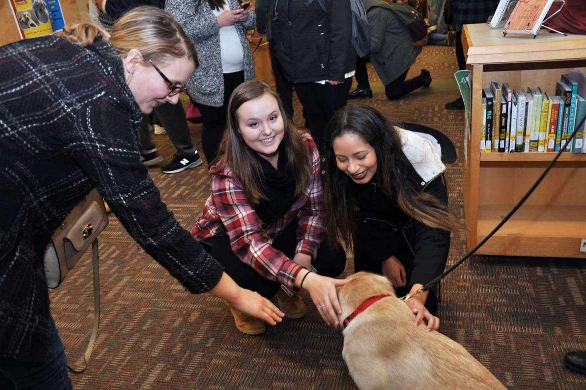 One of the puppies from PurposeFULL Paws enjoys some attention from (l-r) Claire West, a graduate student in college student development from Gerrardstown; Krysetlle Wertheim, a health, physical education, recreation, and sports studies major from Bridgeport; and Cindy Moscote, a business major from Fairfax, Virginia.