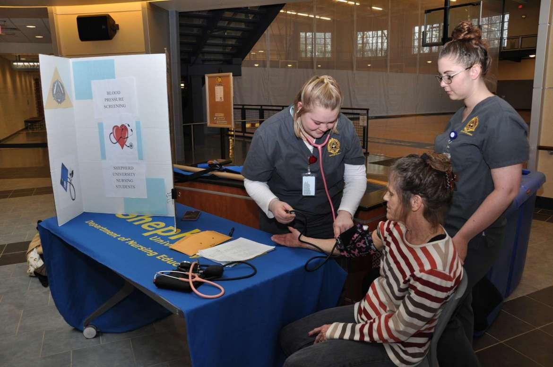 Nursing students Skyler Casto (left) and Stephanie Marchun take a blood pressure reading for Margaret Hoogland in Shepherd University's Wellness Center.