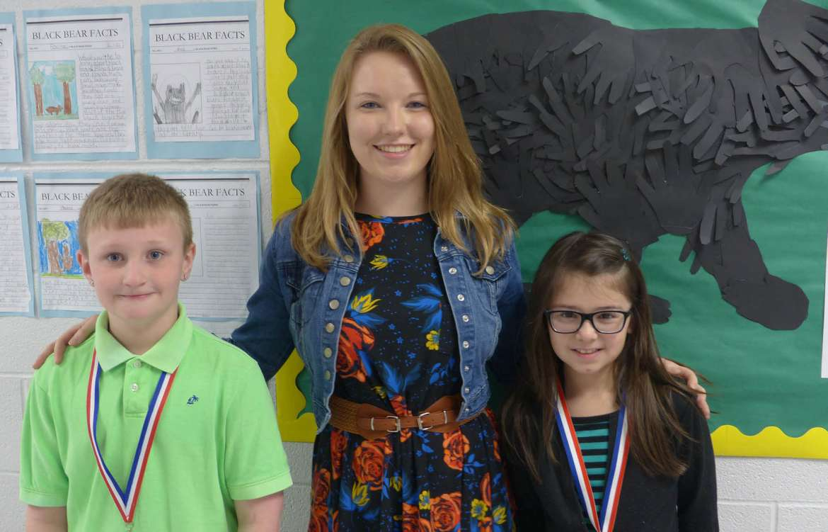 The 2016-2017 National Network of State Teacher of the Year Teacher Candidate Fellowship recipient Ashtyn Bittle, a third grade teacher at Eagle School Intermediate in Martinsburg, stands in front of a black bear class project with students Grayson Mills (l.) and Isabella Silver.
