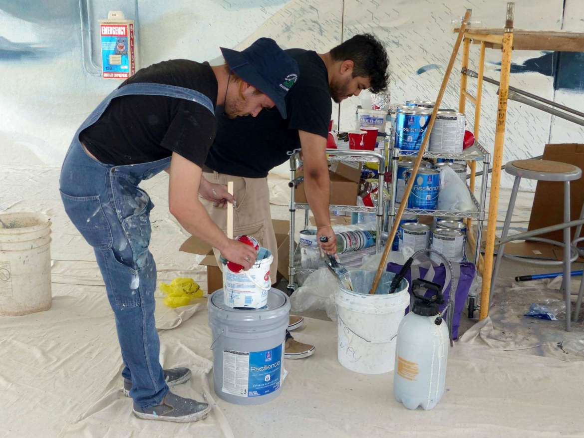 Josh Hawkins and Fernando Velez mix paint for the underpass mural.