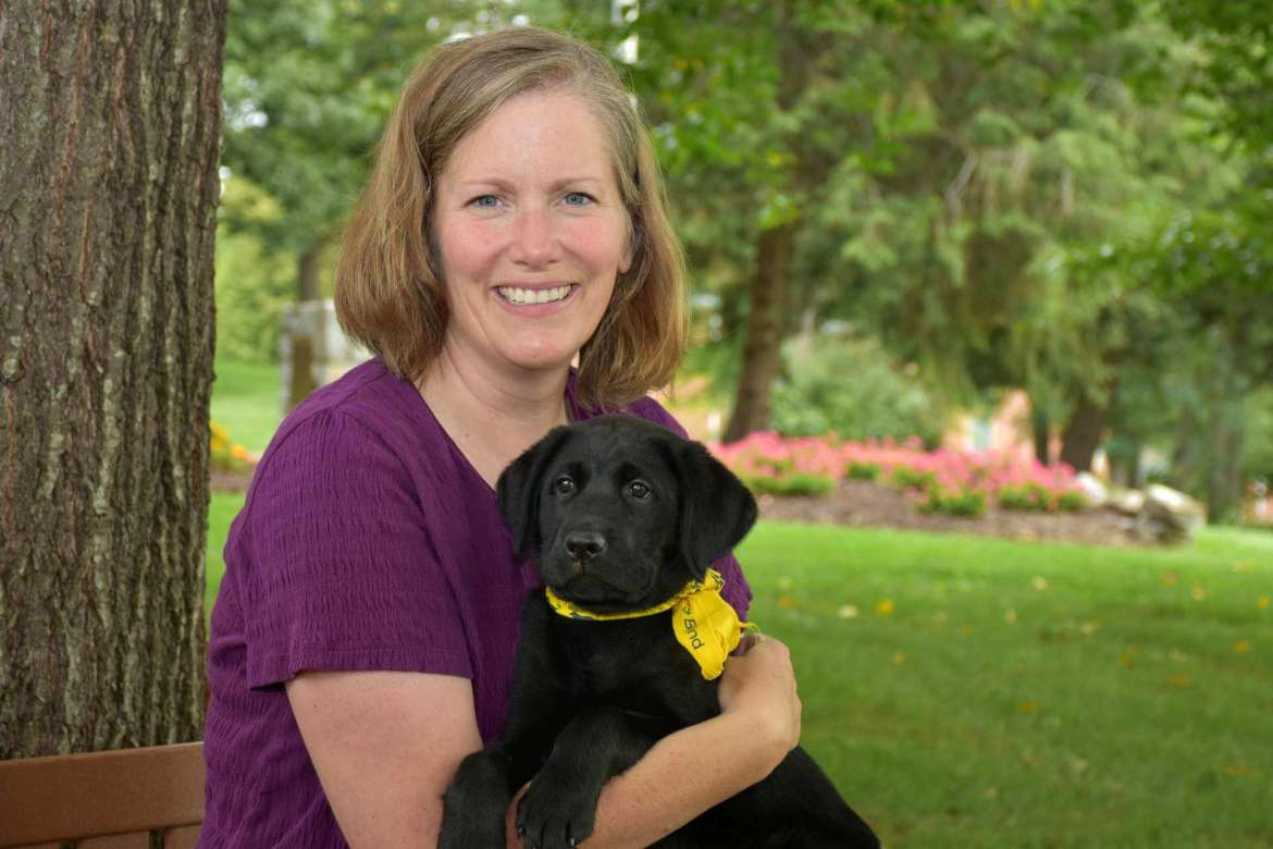 Dr. Amy DeWitt, associate professor of sociology, and Vosco, an 11-week-old black Labrador retriever and a nephew of Luther.
