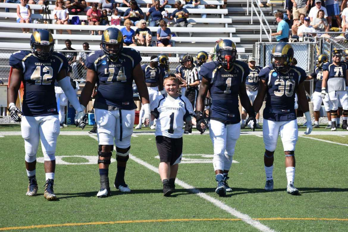 Jason Bednarski (center), of Team IMPACT, serving as honorary team captain for the Shepherd Rams football during the September 23 home game, walks with several Ram players to the center of the field to help with the coin toss.