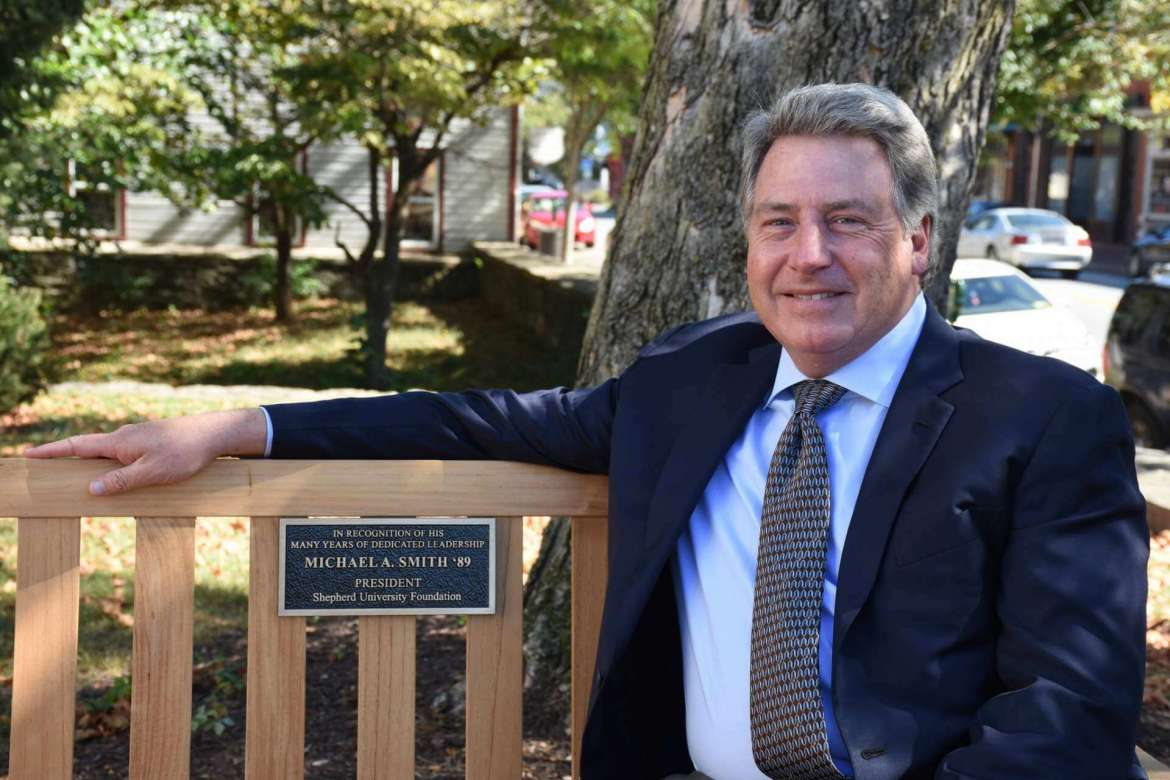 Michael A. Smith, former president of the Shepherd University Foundation, sits on the new teak bench dedicated in his honor along the front walk of McMurran Hall.