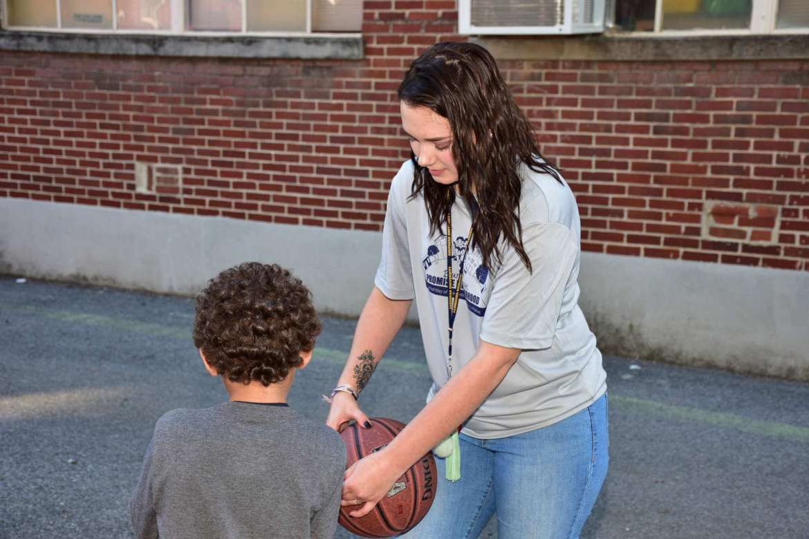 Raina Edwards, a social work major from Inwood, helps a child on the playground of Burke Street Elementary School during the Burke St. Kids program.