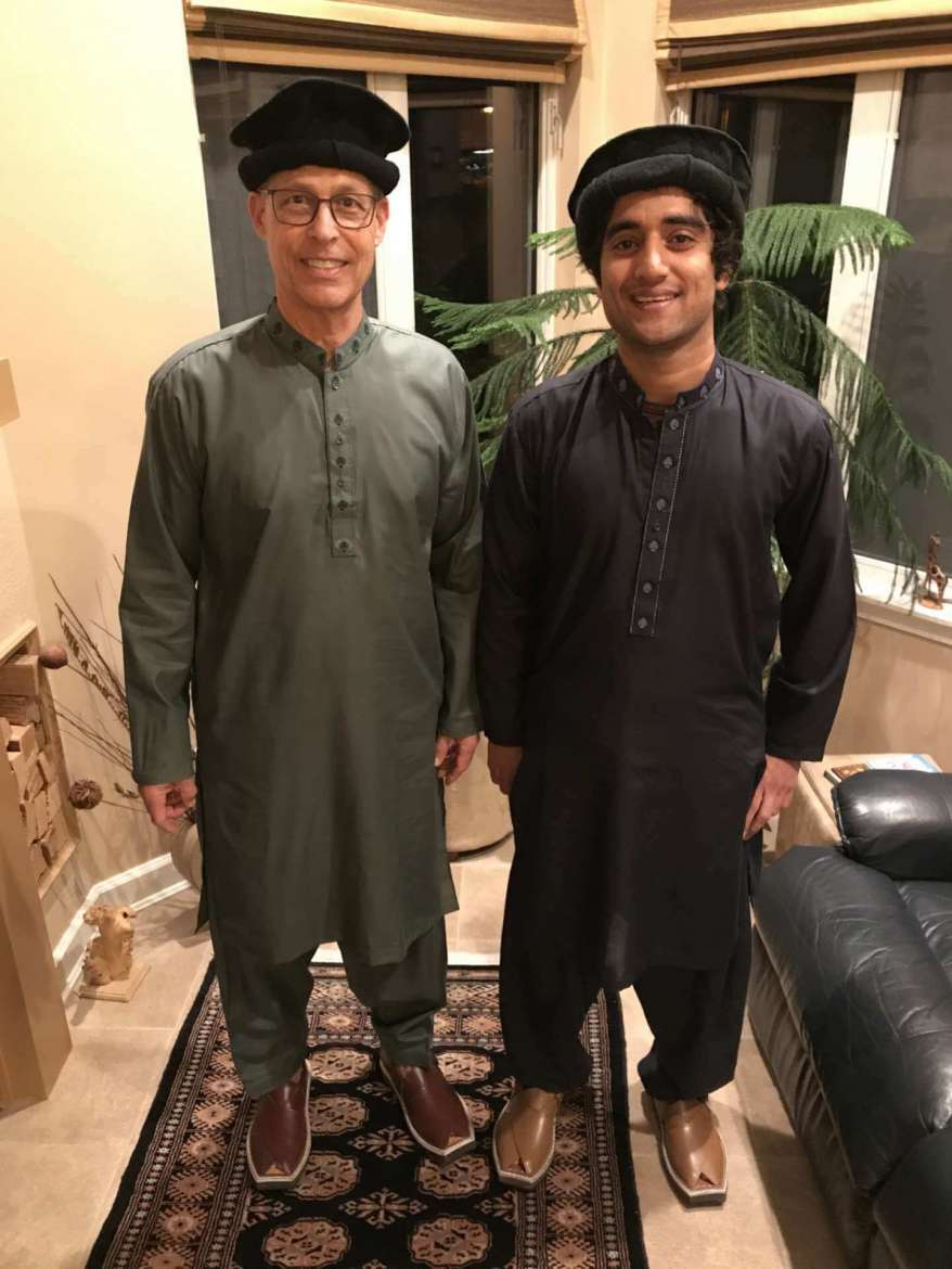 Adnan Haider (r.) is shown with Dr. Charles Nieman, director of international affairs. Both are wearing the dress of Haider's tribe from the Punjab Province, Pakistan. Haider said the cap is called a chitrali cap, the dress is called a kurta, and the shoes are called Peshawri chappal.