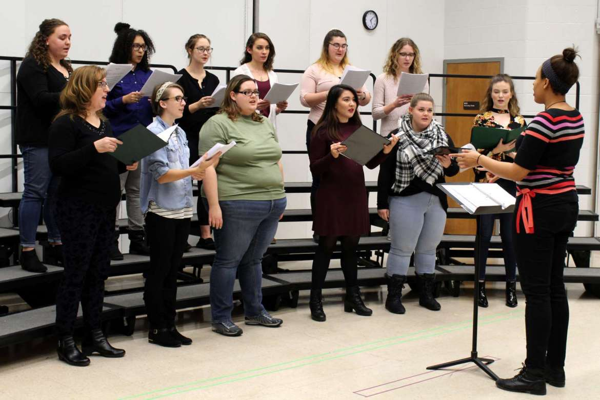 """Tamira Patterson, Westminster, Maryland, conducts as a choir of women rehearsing """"White Bird."""" A recording of the song will be played in the Rude Mechanicals Medieval and Renaissance Players performance of Hrothsvita's """"Thais."""""""