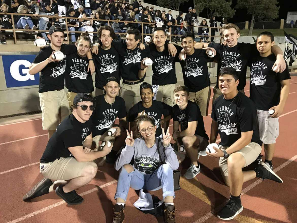 """Emily Keefer poses with the Permian Panthers flag boys during a """"Friday Night Lights"""" football game in Odessa, Texas."""