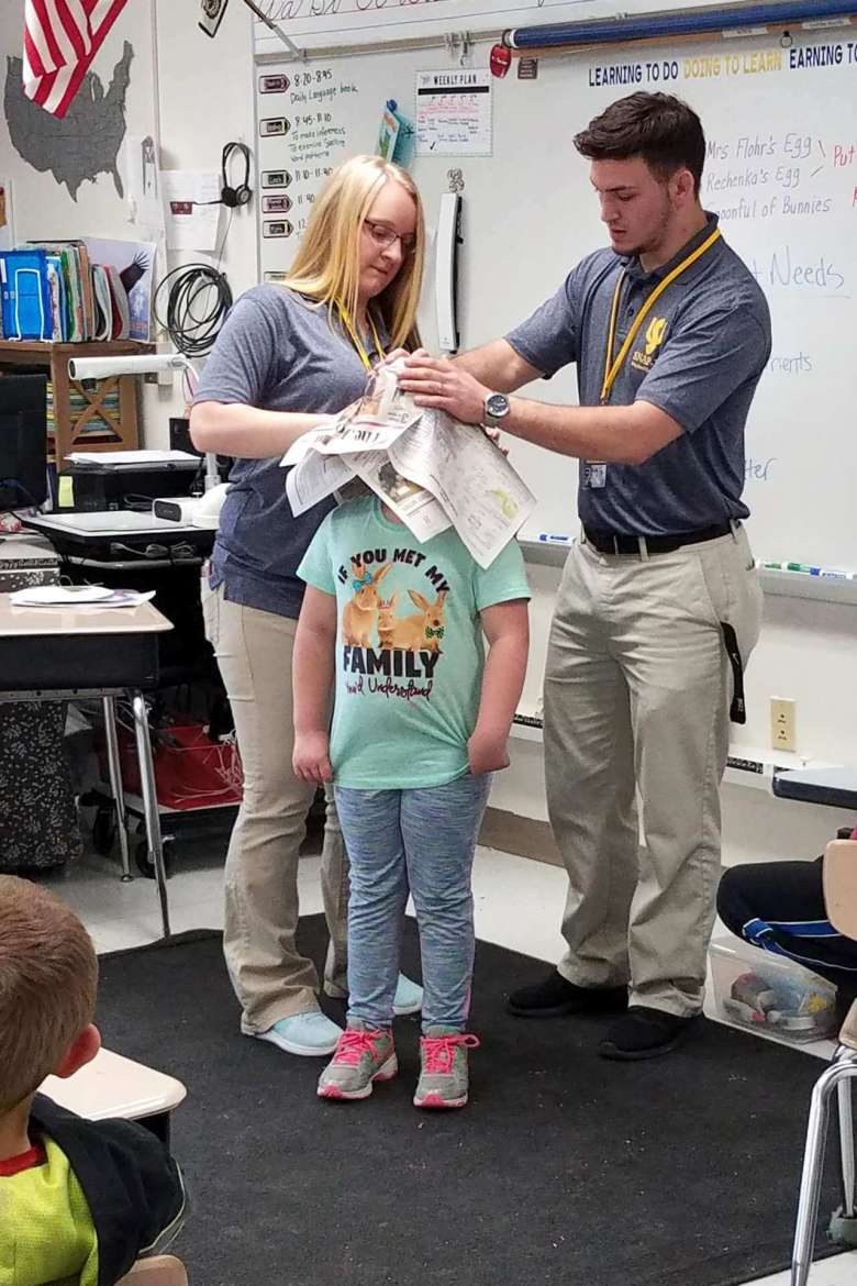 Melissa Varros (left), elementary education major, Mount Airy, Maryland, and Stephen Hite, Regents Bachelor of Arts student, Martinsburg, teach a lesson at Potomack Elementary School in Berkeley County by using a newspaper to make a sombrero hat that will be decorated with symbols representing what each plant needs.