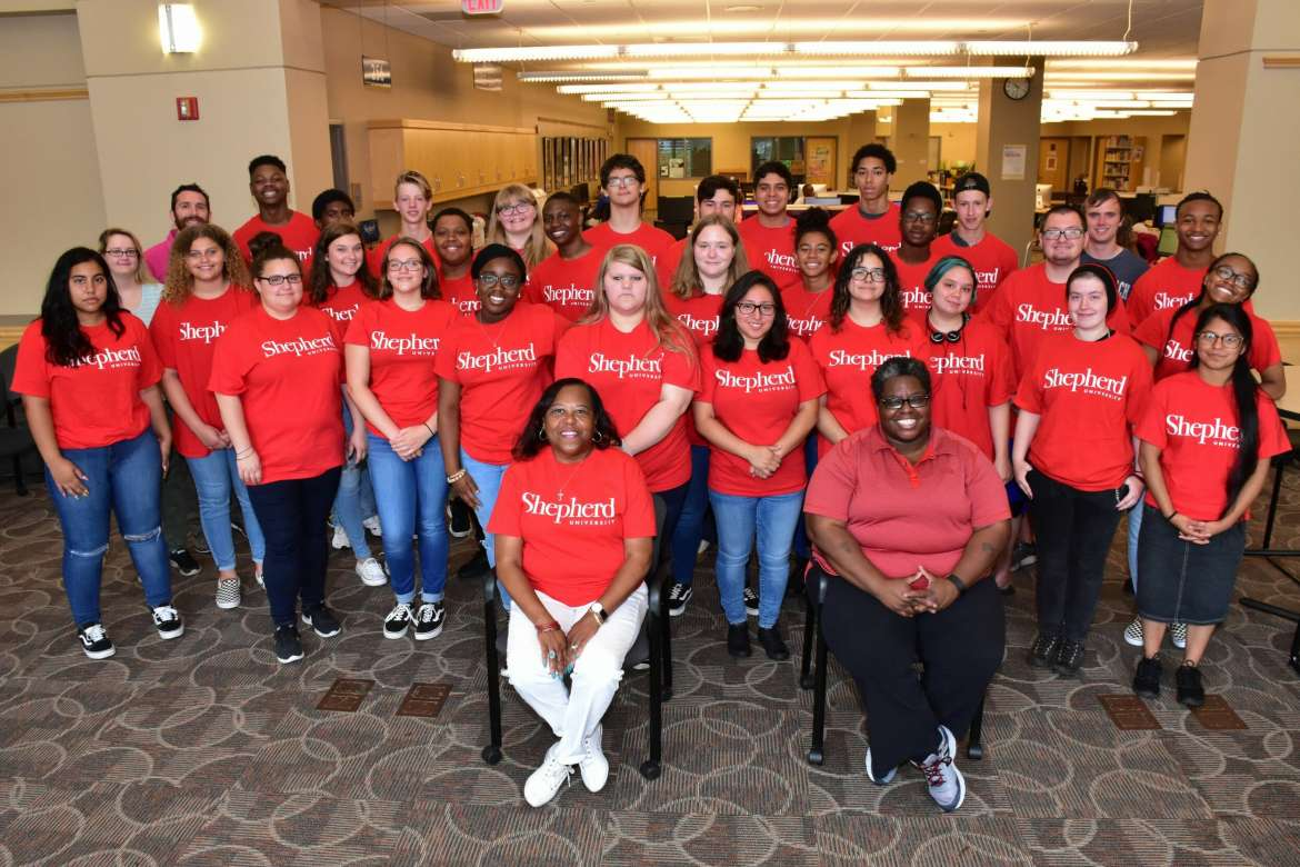 Cynthia Copney, director of TRiO/Student Support Services, (seated l.) and Evora Baker, assistant director of Upward Bound, pose in the Scarborough Library with Upward Bound students from Berkeley County high schools who took classes on Shepherd's campus this summer.