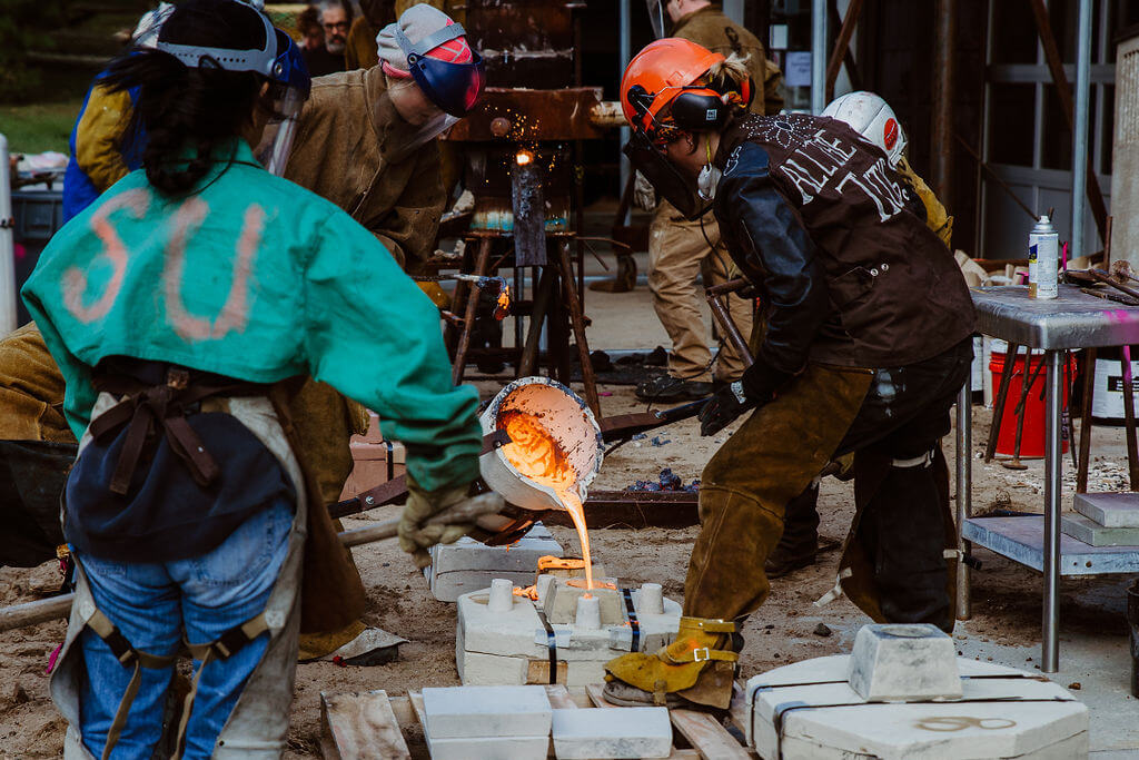 """Alyssa Imes (r.) and her team pour iron into molds at the Women for Shepherd Metal Pour event on October 20. Imes's furnace, """"Phylus,"""" was self-built by the Shepherd University graduate."""