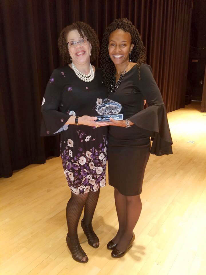 Dr. Chiquita Howard-Bostic (r.), chair of Shepherd's Department of Sociology and Geography, accepts the 2018 Distinguished Alumna Excellence in Advocacy award for the State University of New York at Buffalo Educational Opportunity Program (EOP) award from Denise Hare, EOP academic advisor.