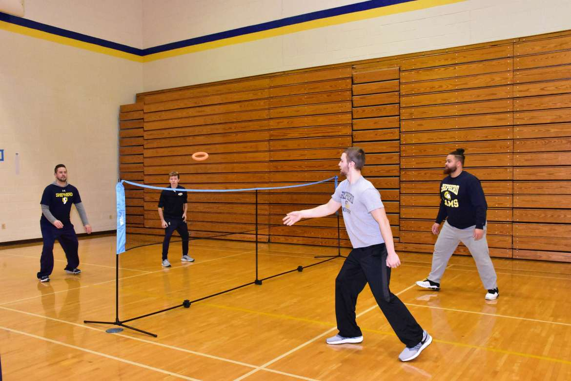 Students in Dr. Jared Androzzi's Teaching Net and Wall Games class play a game of deck tennis.