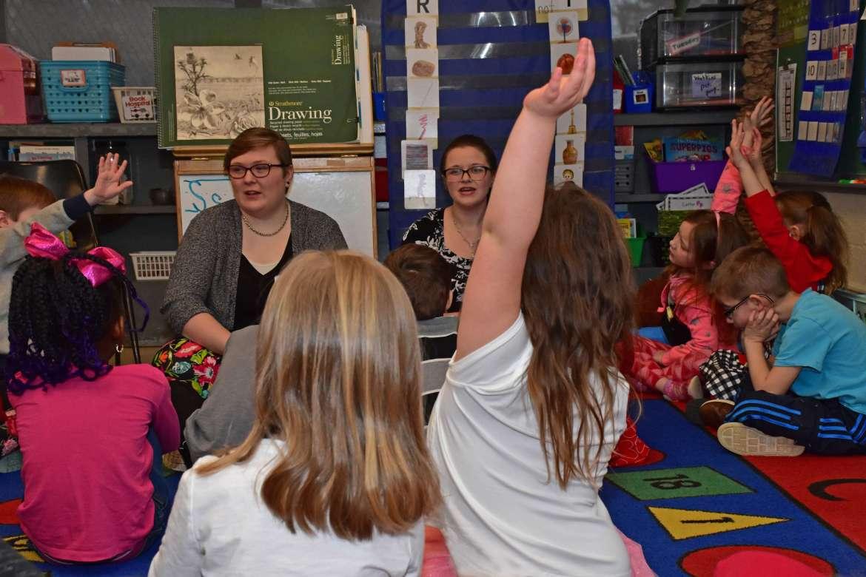 Katlyn Brantner (l.) and Samantha Keplinger work with students in the classroom of kindergarten teacher Melissa Back at Shepherdstown Elementary School.